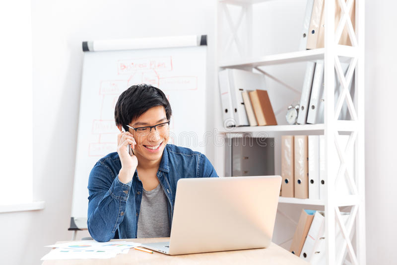 Hombre de negocios usando el ordenador portátil y el hablar en el teléfono celular en oficina fotografía de archivo