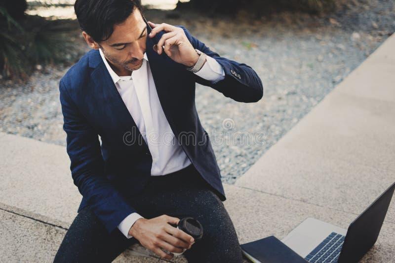 Hombre de negocios usando el smartphone contemporáneo que toma resto fuera de la oficina durante día del trabajo Sosteniéndose la foto de archivo libre de regalías