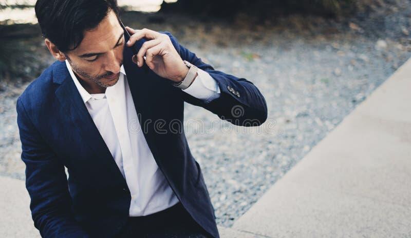 Hombre de negocios usando el smartphone contemporáneo que toma resto fuera de la oficina durante día del trabajo Sosteniéndose la fotos de archivo