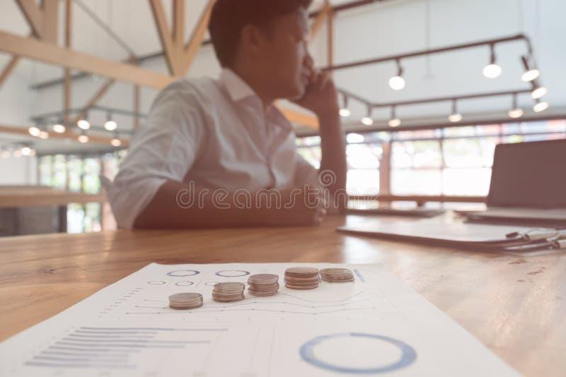 Hombre de negocios usando el teléfono elegante con la moneda del dinero y el gra de la contabilidad foto de archivo