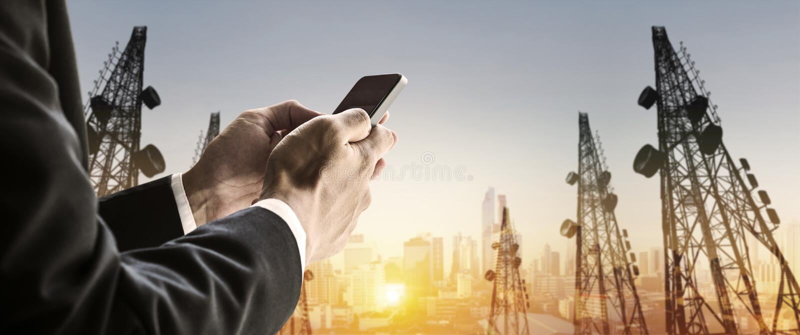 Hombre de negocios usando el teléfono elegante con las torres panorámicas borrosas del paisaje urbano y de la telecomunicación de imagen de archivo