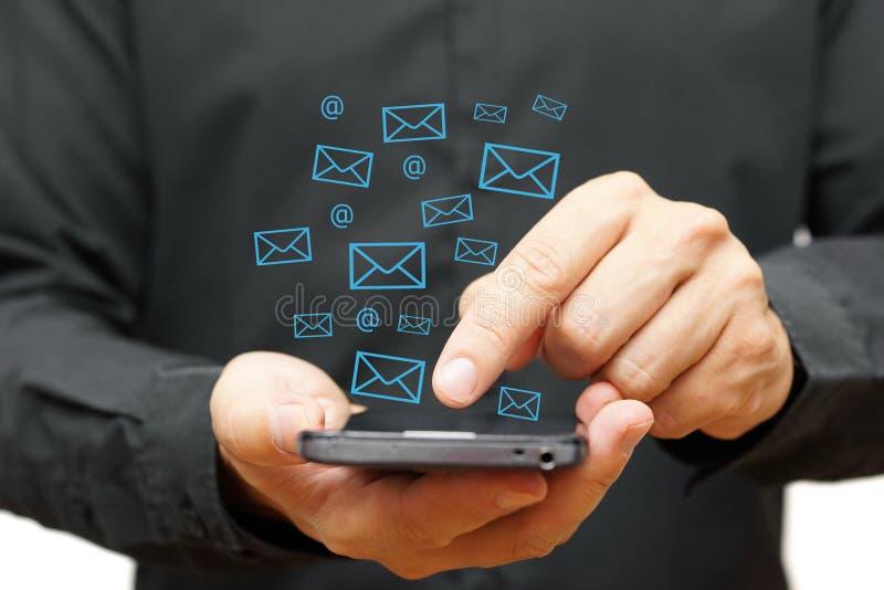 Hombre de negocios usando el teléfono elegante con los iconos del correo electrónico alrededor stock de ilustración
