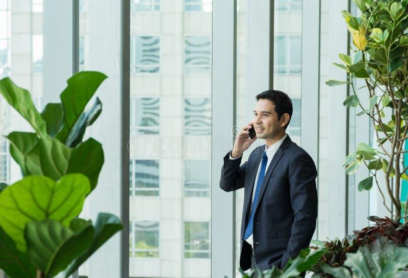 Hombre de negocios usando el teléfono móvil cerca de la ventana de la oficina en las recepciones imagen de archivo libre de regalías