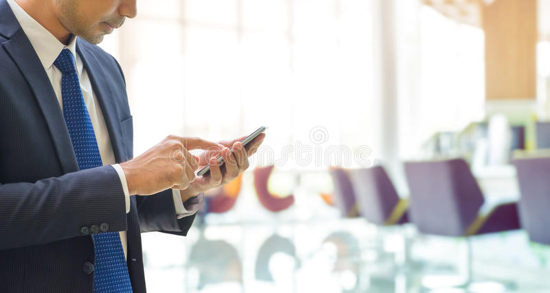 Hombre de negocios usando el teléfono móvil con el fondo de la oficina del banco de la falta de definición foto de archivo libre de regalías