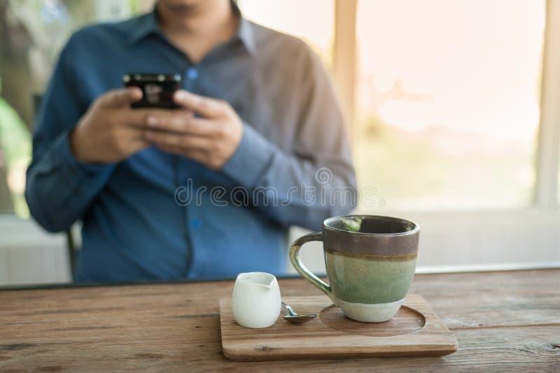 Hombre de negocios usando el teléfono móvil mientras que se sienta en cafetería fotos de archivo