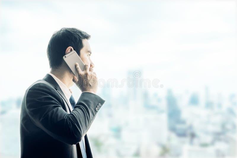 Hombre de negocios usando el teléfono móvil que mira a través de ventana de la oficina a imagen de archivo