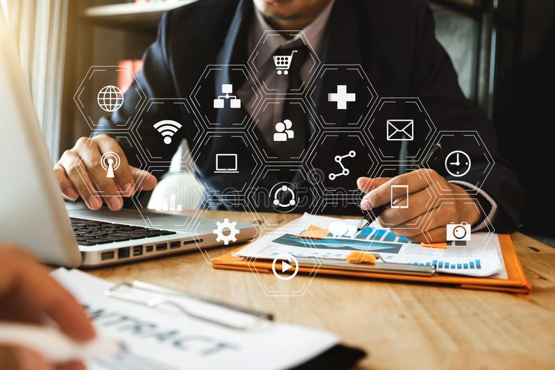 hombre de negocios usando el teléfono móvil y el ordenador portátil en el escritorio de madera imagen de archivo