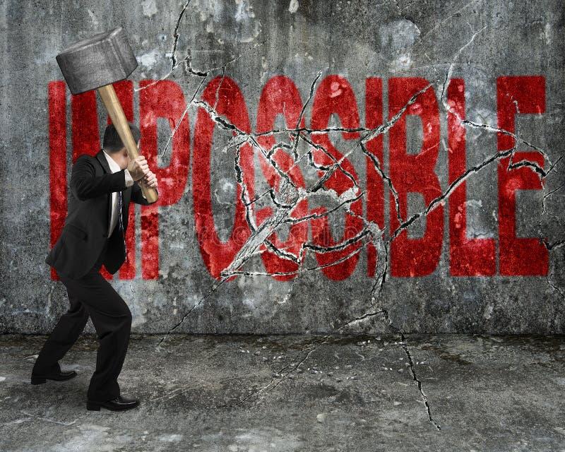 Hombre de negocios usando la almádena que agrieta el brok imposible rojo de la palabra fotos de archivo