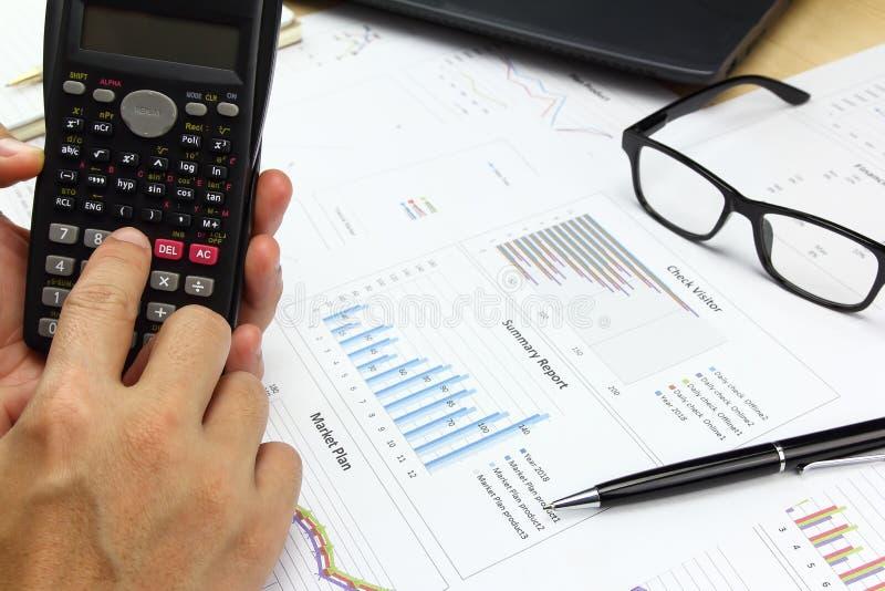Hombre de negocios usando la calculadora con el gráfico de negocio foto de archivo libre de regalías