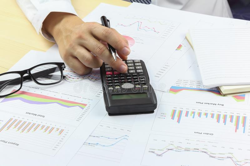 Hombre de negocios usando la calculadora con el gráfico de negocio que analiza compendio imagenes de archivo