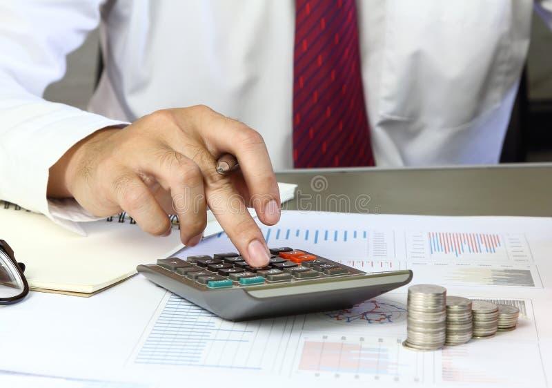Hombre de negocios usando la calculadora con el gráfico de negocio que analiza compendio foto de archivo libre de regalías
