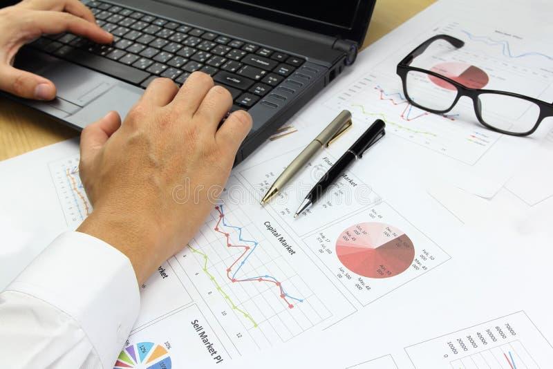 Hombre de negocios usando la calculadora del ordenador con el analyz del gráfico de negocio fotos de archivo libres de regalías