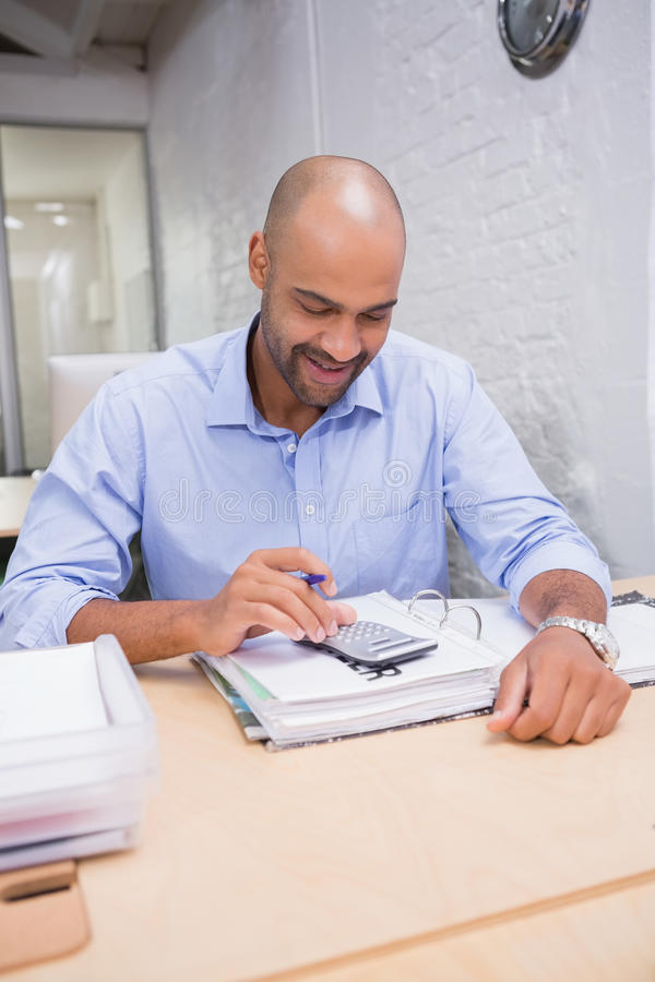 Hombre de negocios usando la calculadora en el escritorio de oficina fotografía de archivo libre de regalías