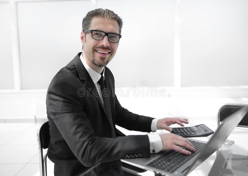 Hombre de negocios usando la calculadora en la mesa de la oficina con el ordenador portátil imágenes de archivo libres de regalías