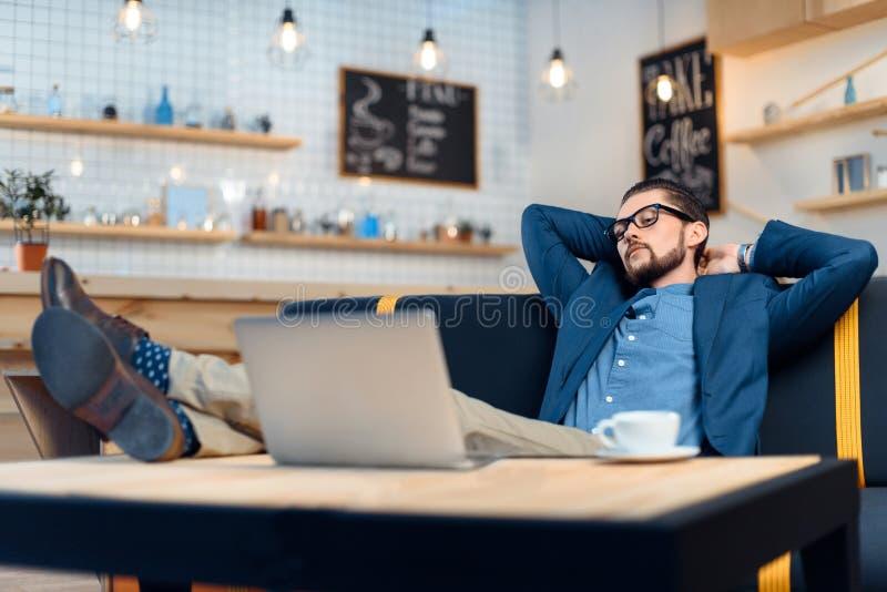 Hombre de negocios usando la computadora portátil en café imagenes de archivo