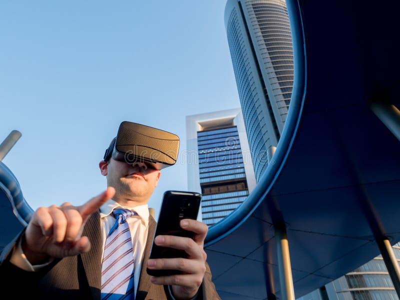 Hombre de negocios usando los vidrios de la realidad virtual con un teléfono móvil adentro fotos de archivo