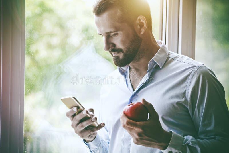Hombre de negocios usando manzana elegante del teléfono y de la consumición imagenes de archivo