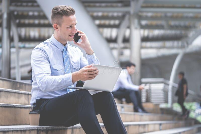 Hombre de negocios usando sentarse del teléfono móvil al aire libre imagen de archivo libre de regalías