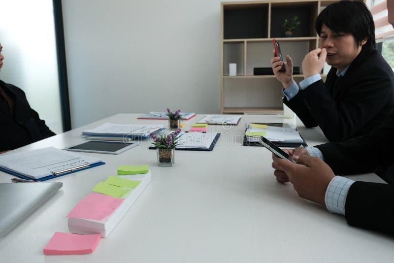 Hombre de negocios usando smartphone en sala de reunión hombre que sostiene el móvil foto de archivo