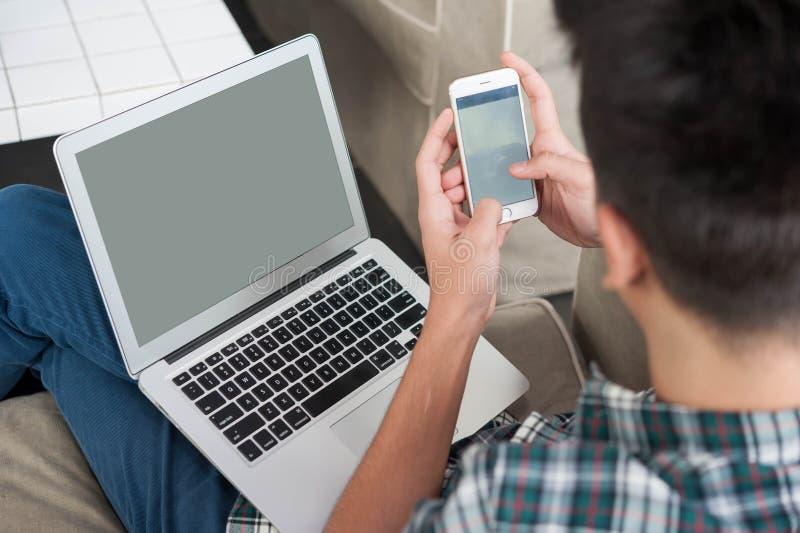 Hombre de negocios usando smartphone y ordenador portátil en el sofá foto de archivo
