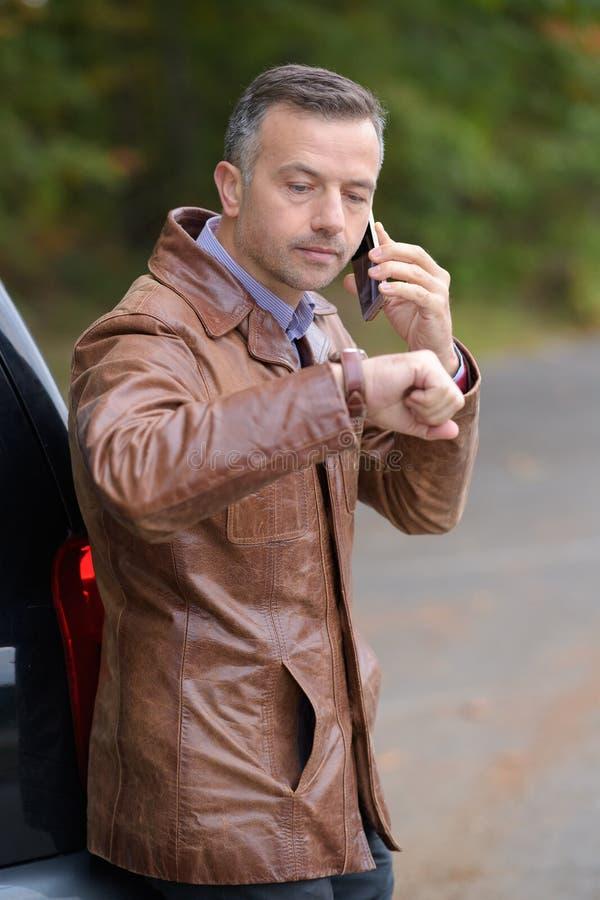 Hombre de negocios usando smartphone y tiempo de observación foto de archivo libre de regalías