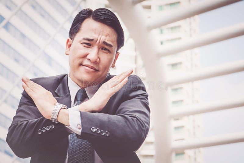 Hombre de negocios usando su brazo como como cruz, significado mal foto de archivo