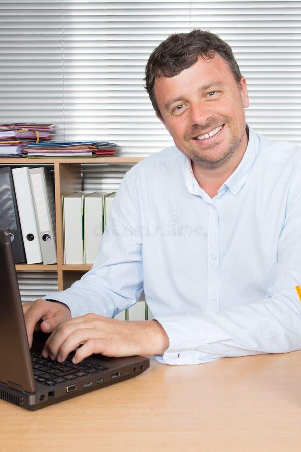 Hombre de negocios usando su ordenador en su oficina imágenes de archivo libres de regalías