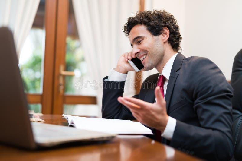 Hombre de negocios usando su ordenador portátil mientras que habla en el teléfono fotografía de archivo libre de regalías