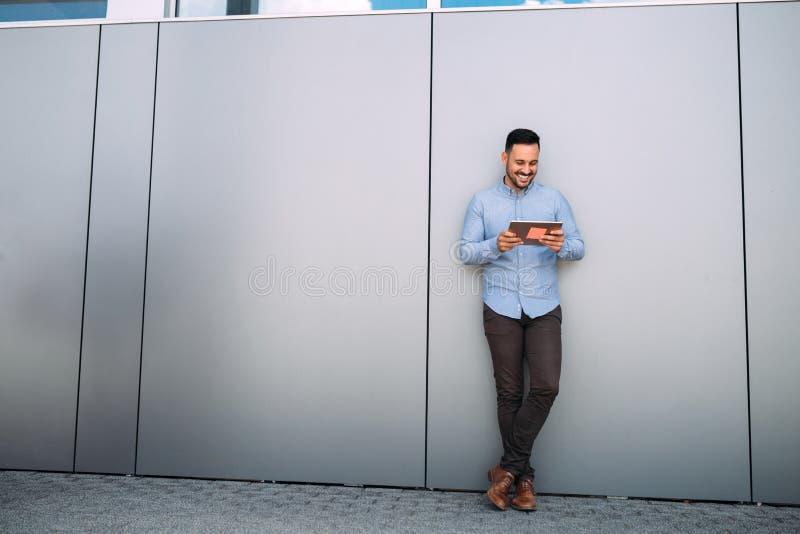 Hombre de negocios usando su tableta digital cerca de una pared fotos de archivo