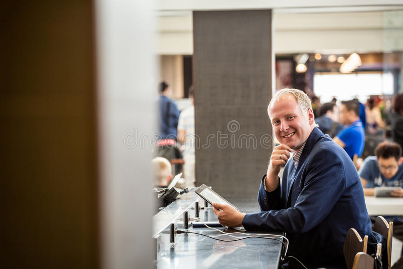 Hombre de negocios usando su tableta en el aeropuerto imágenes de archivo libres de regalías