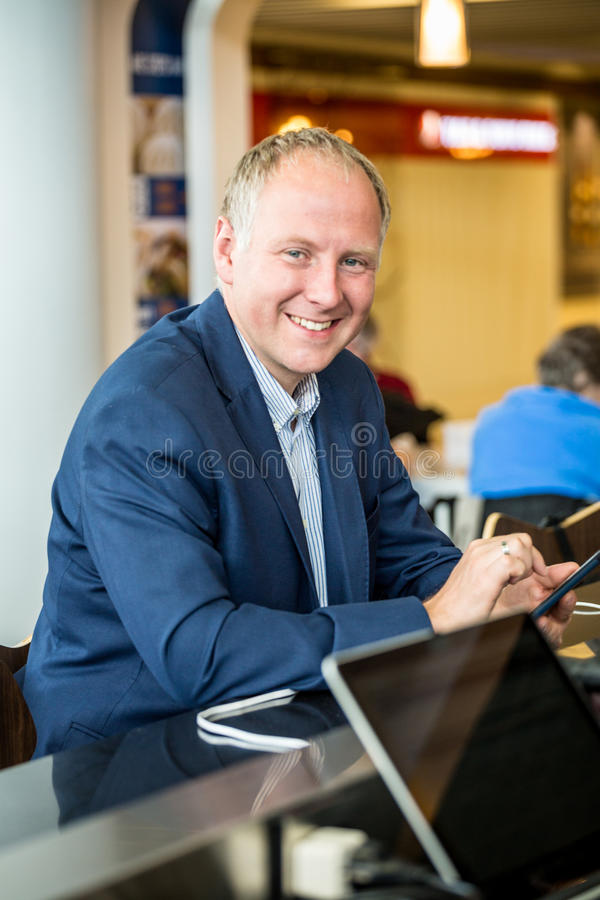 Hombre de negocios usando su tableta en el aeropuerto fotografía de archivo