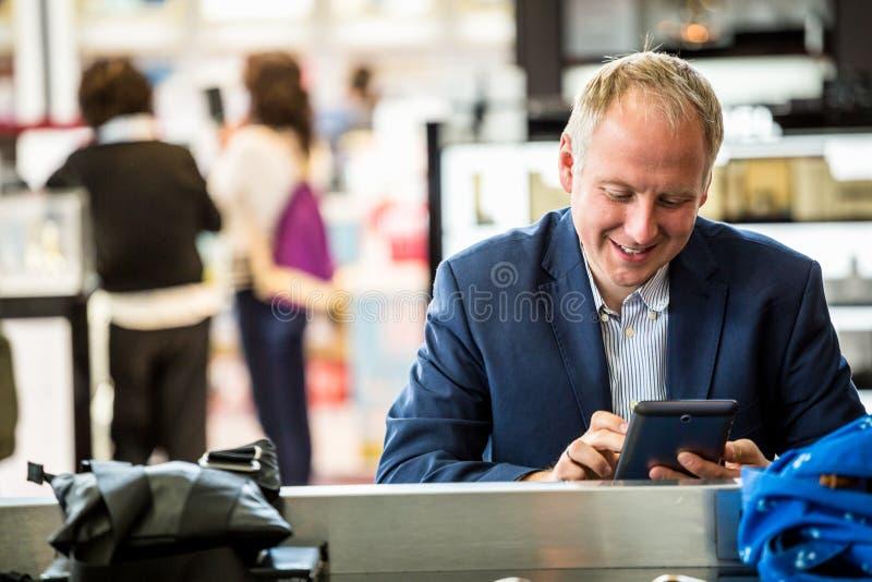 Hombre de negocios usando su tableta en el aeropuerto fotos de archivo