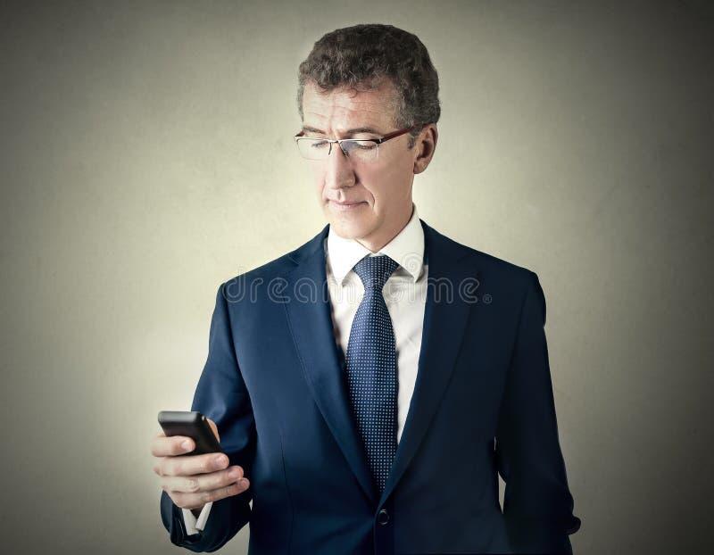 Hombre de negocios usando un teléfono elegante imagenes de archivo