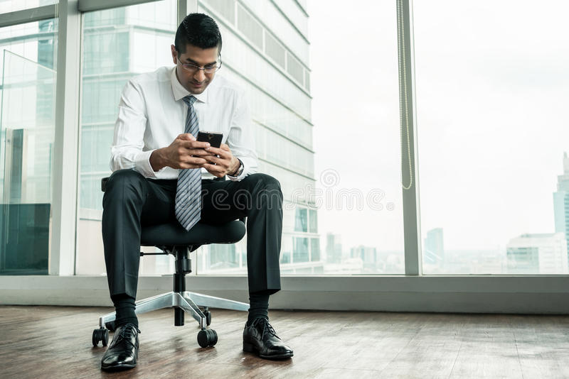 Hombre de negocios usando un teléfono móvil mientras que se sienta imágenes de archivo libres de regalías