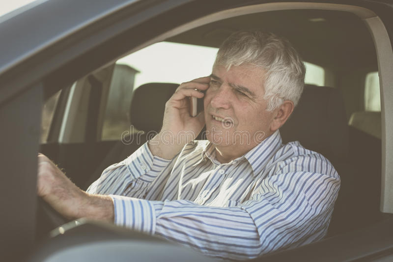 Hombre de negocios usando un teléfono, sentándose en coche fotografía de archivo libre de regalías