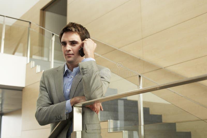 Hombre de negocios Using Cellphone While que se inclina en la verja de cristal imagen de archivo