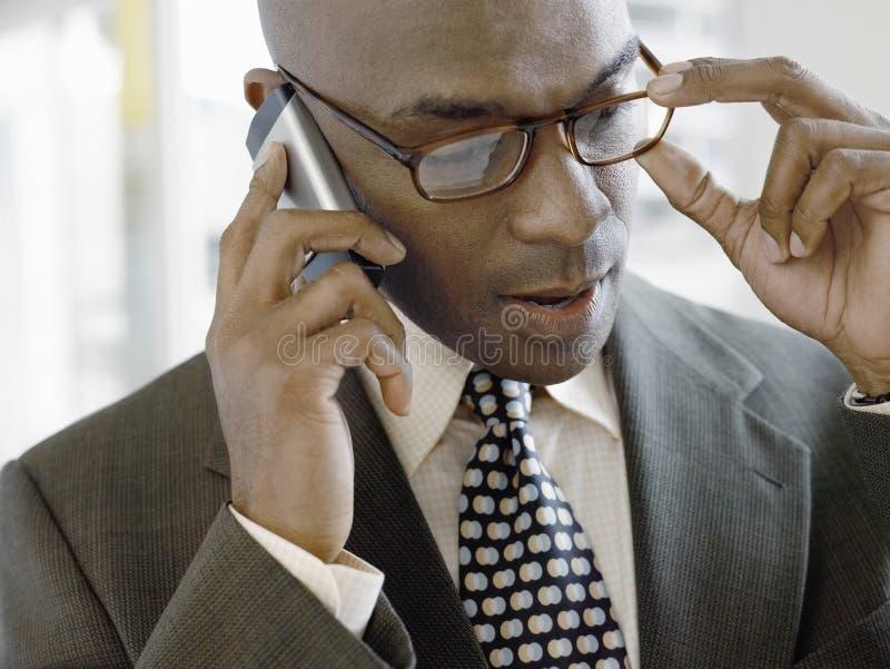 Hombre de negocios Using Mobile Phone mientras que lleva los vidrios en oficina foto de archivo libre de regalías