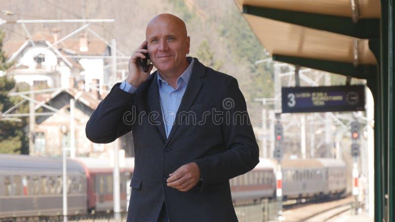 Hombre de negocios Waiting y el hablar con el teléfono móvil en una estación de tren fotos de archivo libres de regalías