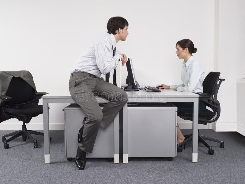 Hombre de negocios Watching Female Colleague en oficina imagen de archivo libre de regalías