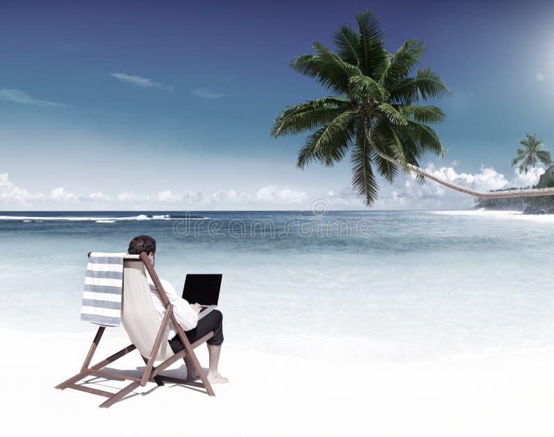Hombre de negocios Working en un concepto tropical de la playa foto de archivo