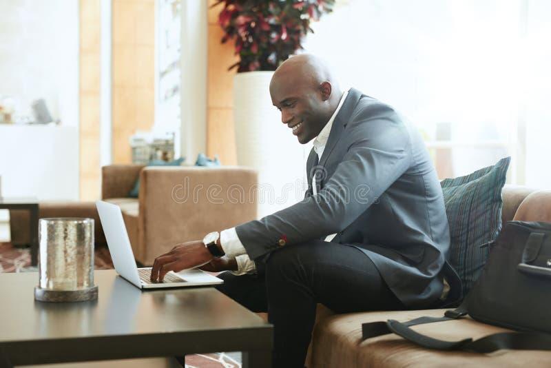 Hombre de negocios Working On Laptop en pasillo del hotel foto de archivo libre de regalías