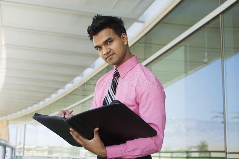 Hombre de negocios Writing In un planificador imagen de archivo libre de regalías