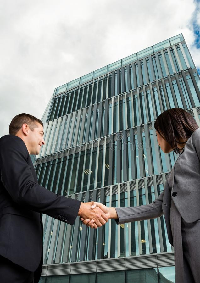 hombre de negocios y apretón de manos de la mujer delante del edificio fotos de archivo libres de regalías