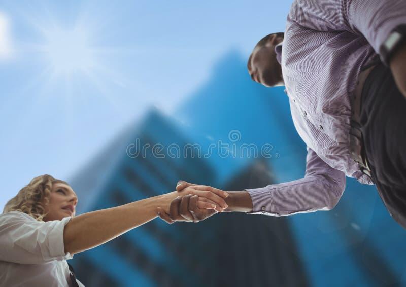 Hombre de negocios y apretón de manos de la mujer Opinión del cielo Ciudad foto de archivo