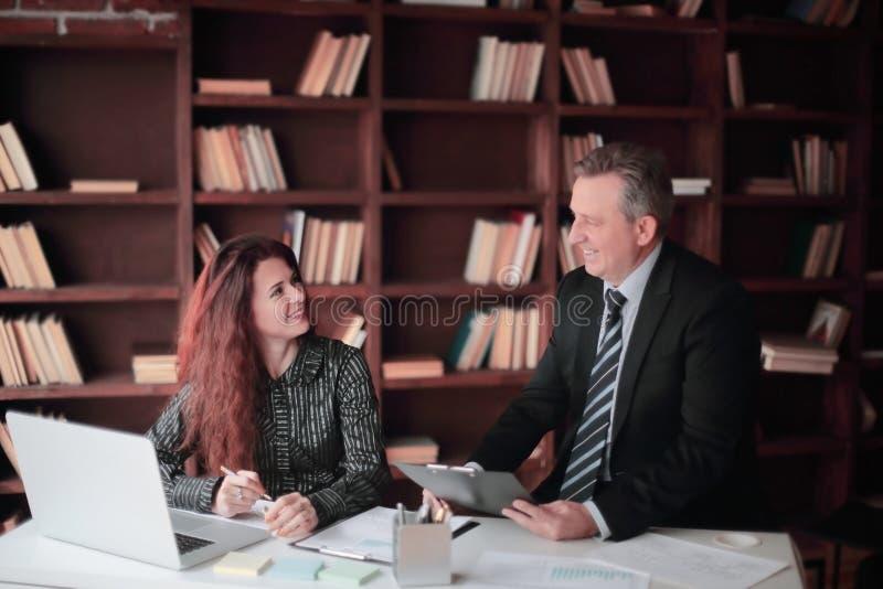 Hombre de negocios y ayudante que discuten un documento de trabajo fotos de archivo