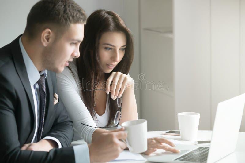 Hombre de negocios y empresaria en el escritorio de oficina, mirando el revestimiento fotos de archivo libres de regalías