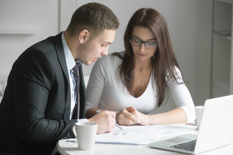 Hombre de negocios y empresaria en el escritorio de oficina, trabajando junto w imagen de archivo libre de regalías