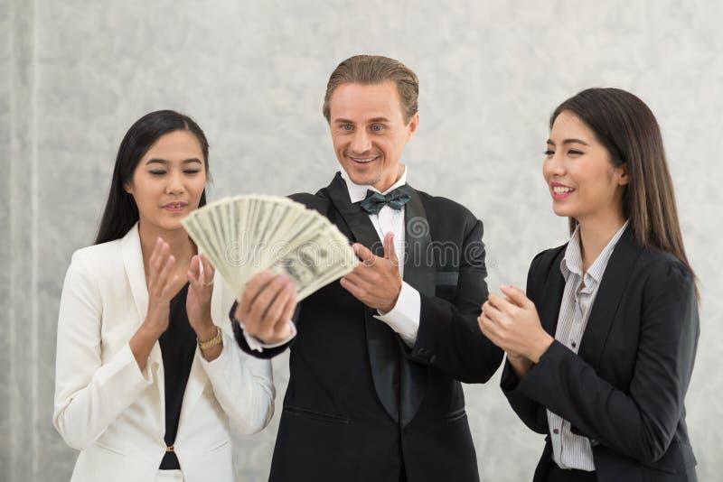 Hombre de negocios y empresaria felices con la demostración del dinero successf imagen de archivo