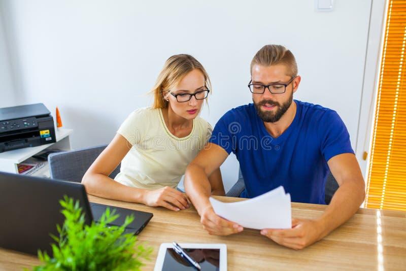 Hombre de negocios y empresaria que analizan algunos documentos Negocios imágenes de archivo libres de regalías