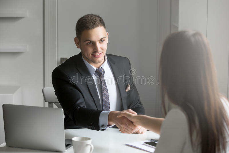 Hombre de negocios y empresaria que sacuden las manos en el acuerdo imagen de archivo libre de regalías